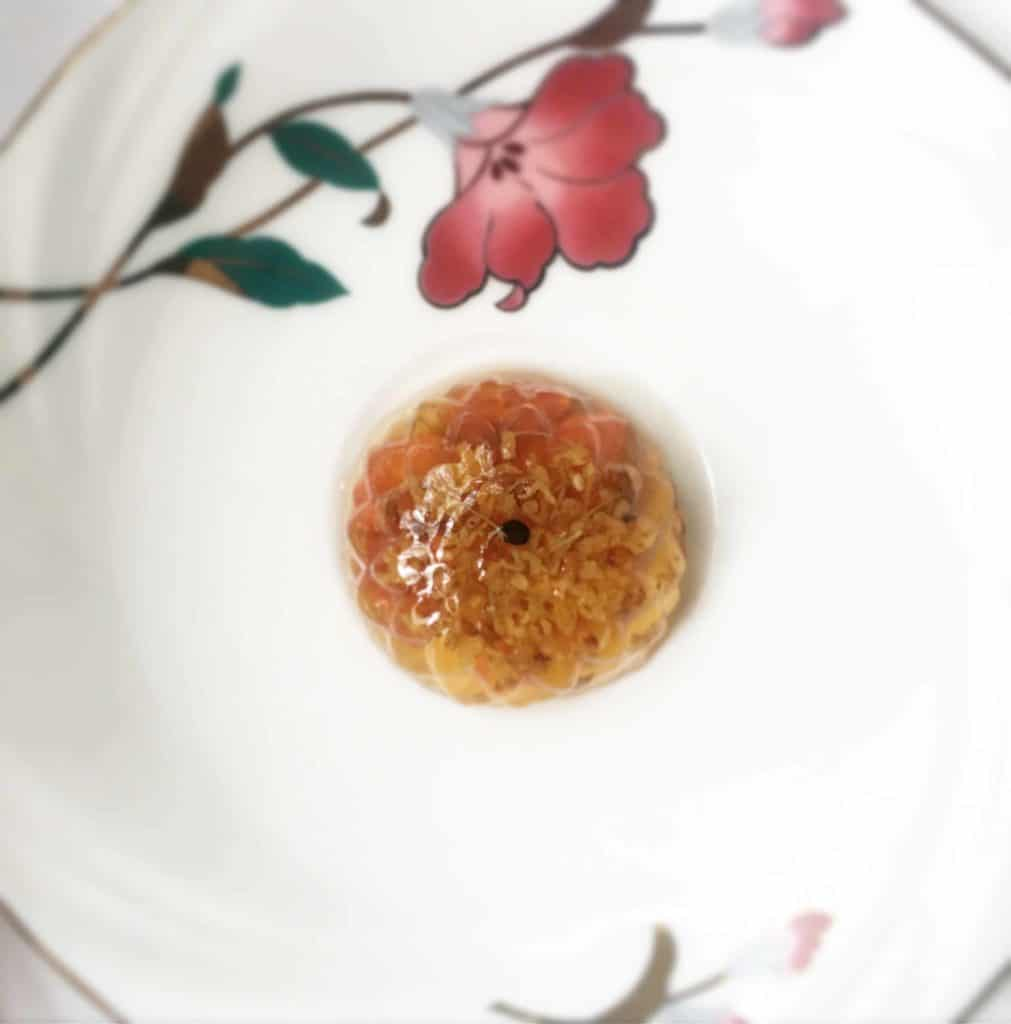 Flower Shaped Osmanthus Konnayku Jelly with Wolfberries on a plate