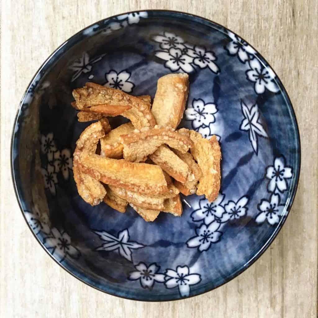 Crispy pork crackling in a blue bowl