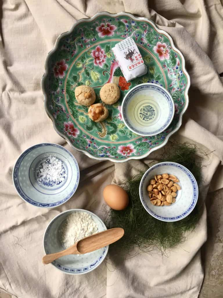 Chinese peanut cookies on a plate with its ingredients peanuts, peanut oil, flour, sugar and egg