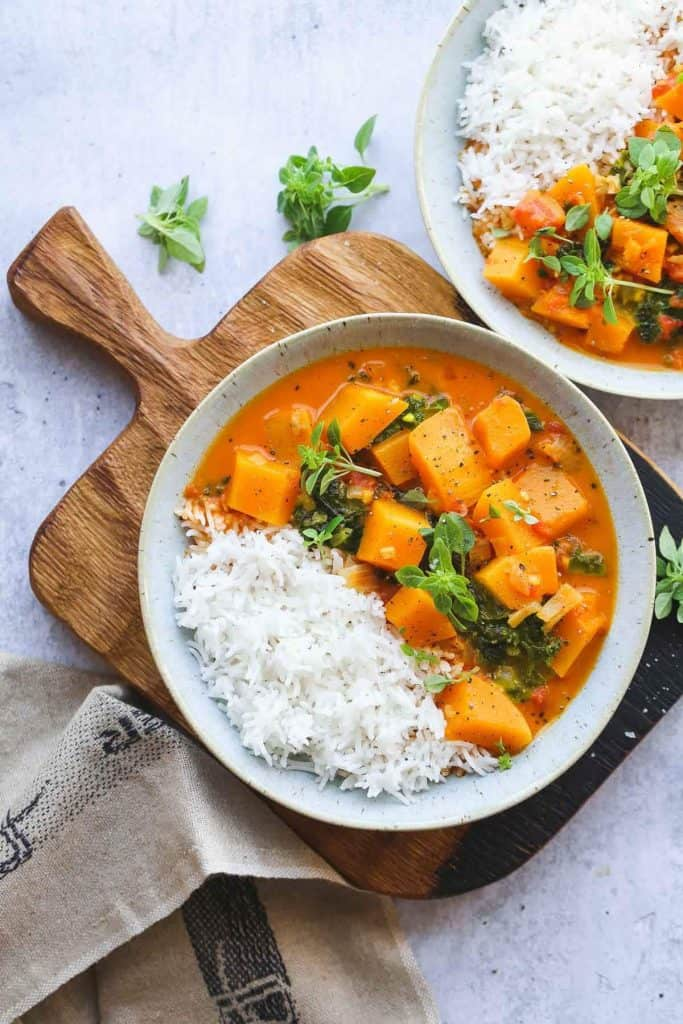 Bowl of lemongrass butternut squash curry with rice and garnished with herbs