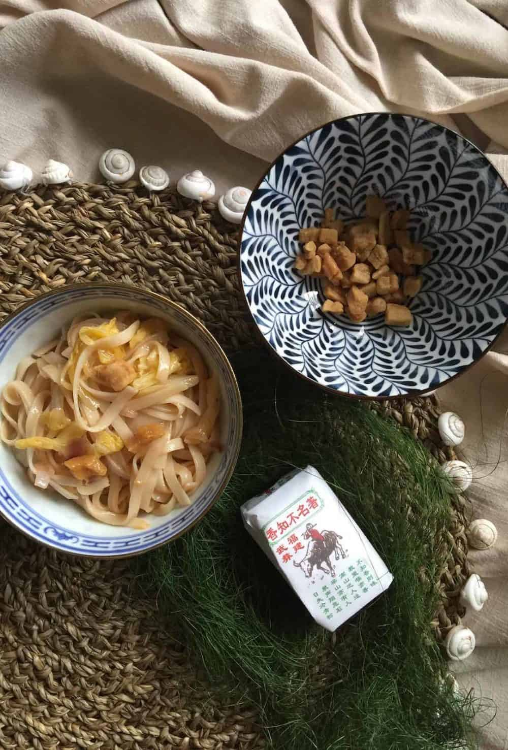 A bowl of noodles fried in pork lard, a bowl of crispy pork scratchings and a packet of chinese tea