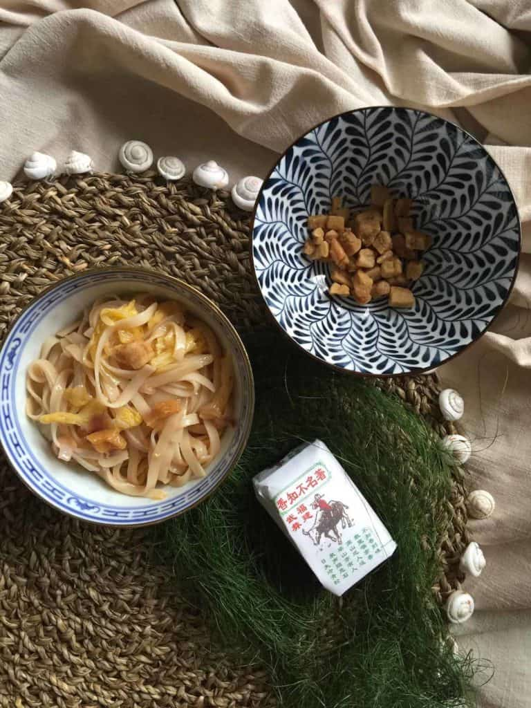 A bowl of noodles fried in pork lard next to a bowl of crispy pork lardons and a packet of chinese tea