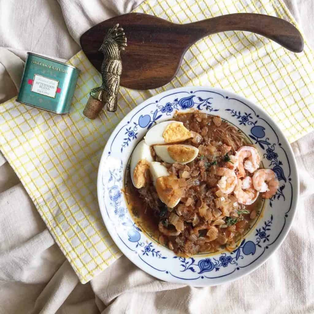 A bowl of Peranakan mee siam noodles with gravy, garnishes with prawns and egg