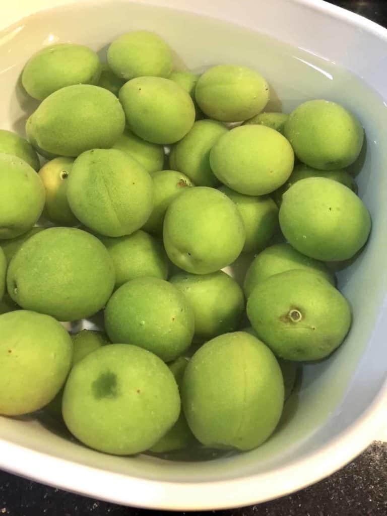 Green maesil soaking in baking soda to remove pesticides
