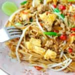 A fork dipped into a plate of Pad Mee Korat, a Northeastern Thai spicy stir fried noodle